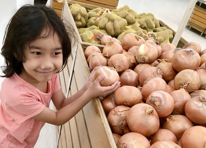 Close-up of girl holding onion at market