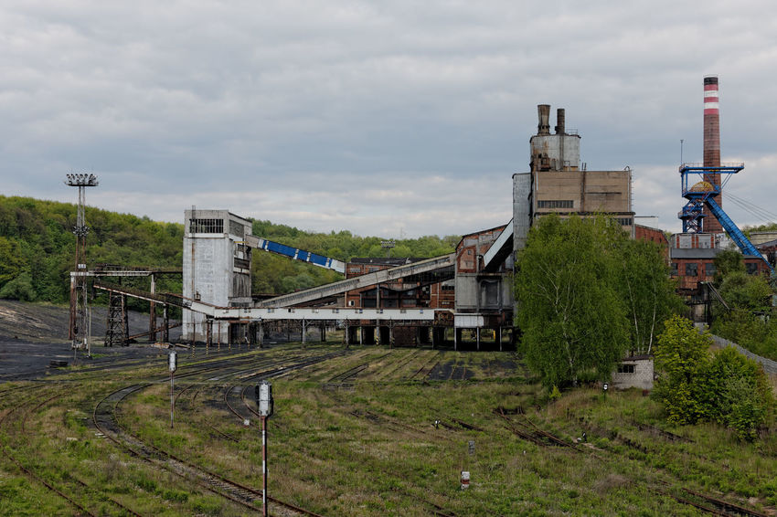 An old coal mine in Poland. Coal Mine Poland Architecture Building Building Exterior Built Structure City Cloud - Sky Day Factory High Angle View Industry Nature No People Old Old Coal Mine Outdoors Plant Rail Transportation Railroad Track Sky Smoke Stack Track Transportation