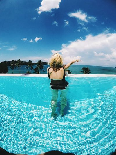 Rear view of woman gesturing swimming in pool by sea against sky