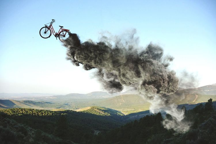 Digital Composite Image Of Smoke Reaching Bicycle In Mid-Air Over Rolling Landscape