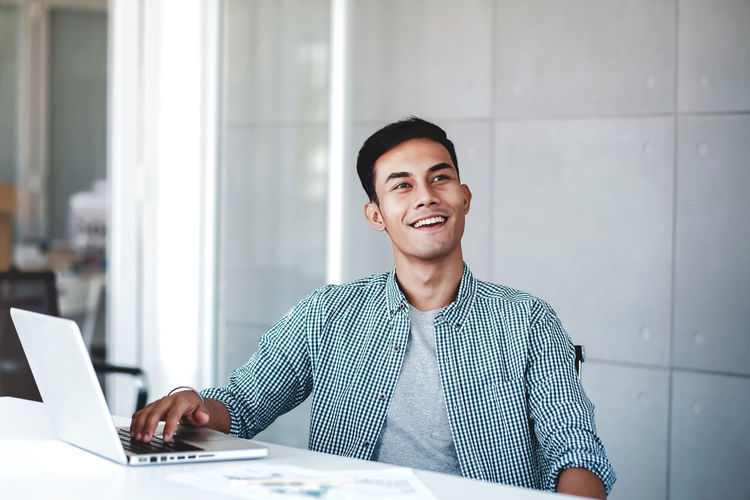 Happy Young Businessman Working on Computer Laptop in Office. Smiling and looking away Laptop Computer Wireless Technology Using Laptop One Person Smiling Technology Young Adult Sitting Casual Clothing Table Communication Front View Connection Waist Up Young Men Men Adult Indoors  Looking At Camera Looking Away Office Asian  Happy Working