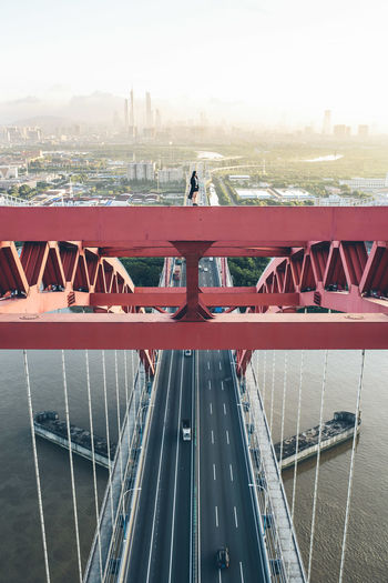 Woman standing on cable-stayed bridge over river in city