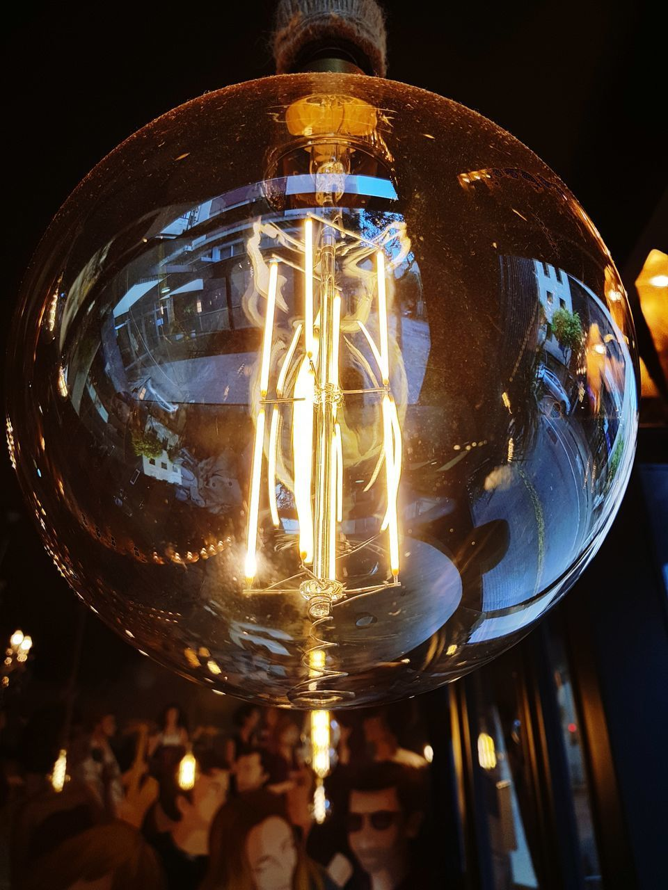 LOW ANGLE VIEW OF ILLUMINATED LIGHT BULB HANGING IN DARK
