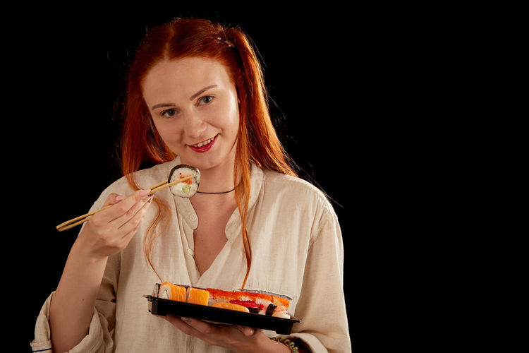 Portrait of smiling young woman eating food against black background