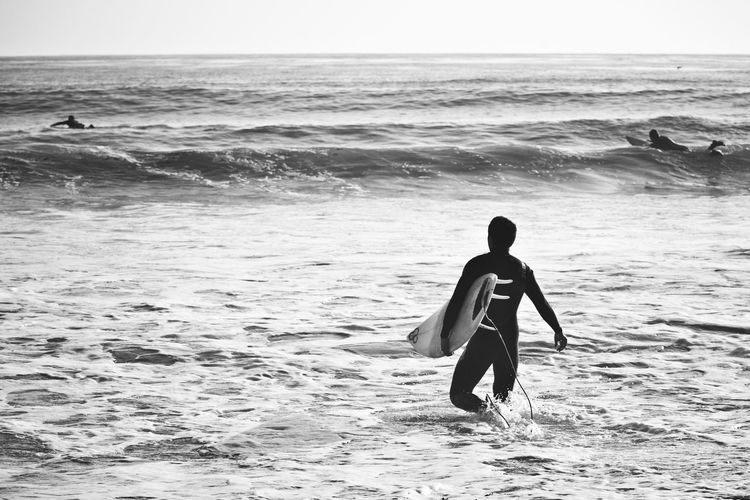 Beach Beauty In Nature Children Only Day Extreme Sports Full Length Horizon Over Water Leisure Activity Lifestyles Men Motion Nature One Person Outdoors People Real People Rear View Scenics Sea Sky Sport Surfboard Vacations Water Wave