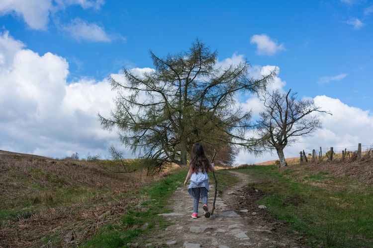 a young girl on a Scottish hiking trail Full Length Sky Cloud - Sky One Person Plant Tree Nature Day Land Non-urban Scene Casual Clothing Real People Leisure Activity Environment Landscape Rear View Field Scenics - Nature Women Hairstyle Outdoors