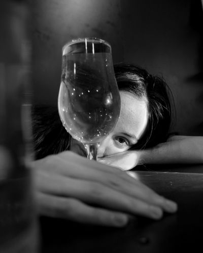 Portrait of woman drinking glass on table