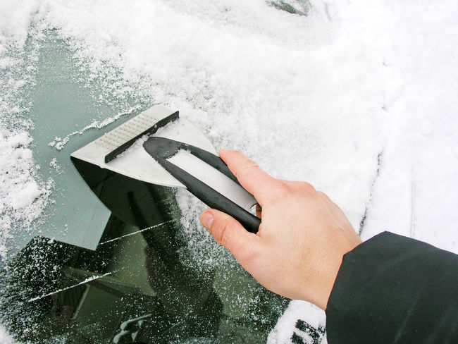 Mann cleaning windscreen from ice with a ice scraper Cleaning Driving Frost Ice Man Morning Weather Winter Wintertime Baden Württemberg Car Forecast Frosty Germany Hand Holding Ice Scraper Outdoors Safety Save Scrape Snow Snowing Technology Windscreen