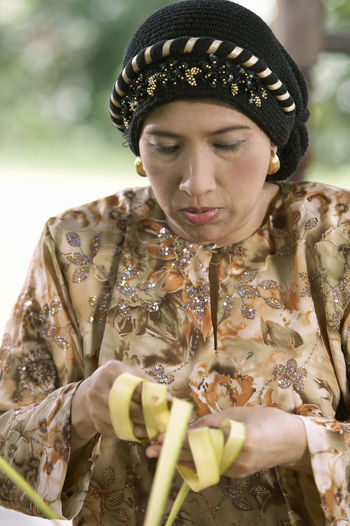 Close-up of woman weaving leaves while sitting in gazebo