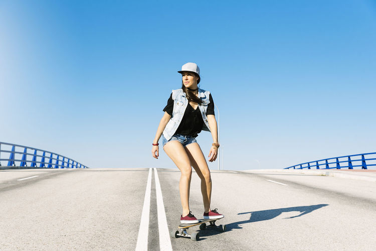 Woman skateboarding against blue sky