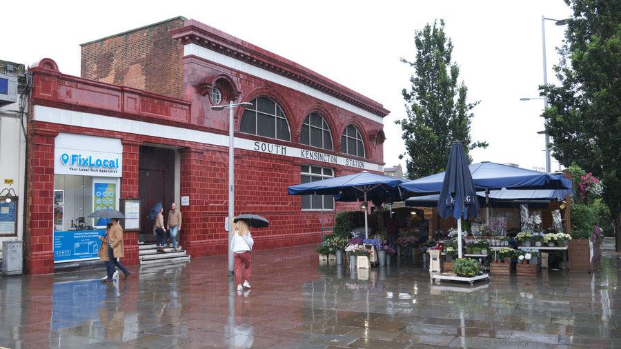 People on wet building against sky during rainy season