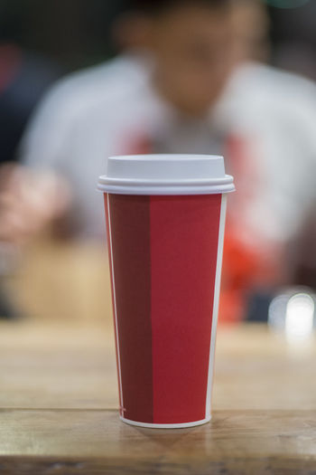 One tall cup of coffee! Food And Drink Drink One Person Refreshment Focus On Foreground Red Cup Drinking Glass Table Glass Disposable Men Coffee Lifestyles Coffee - Drink Disposable Cup Incidental People Holding Hot Drink Drinking