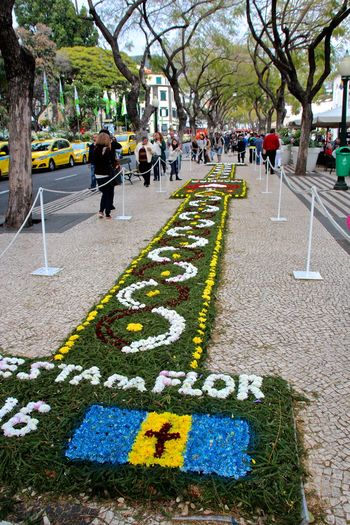 People By Decorations With Text On Footpath In City
