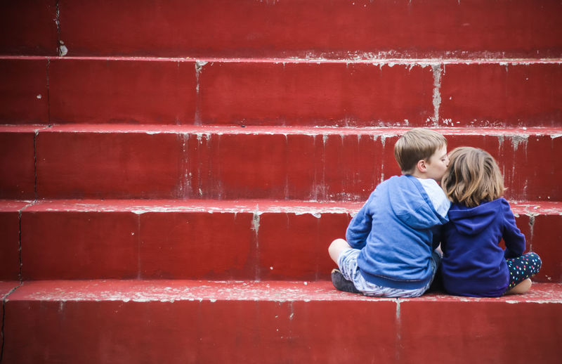 Rear view of boy kissing a girl and sitting against red wall
