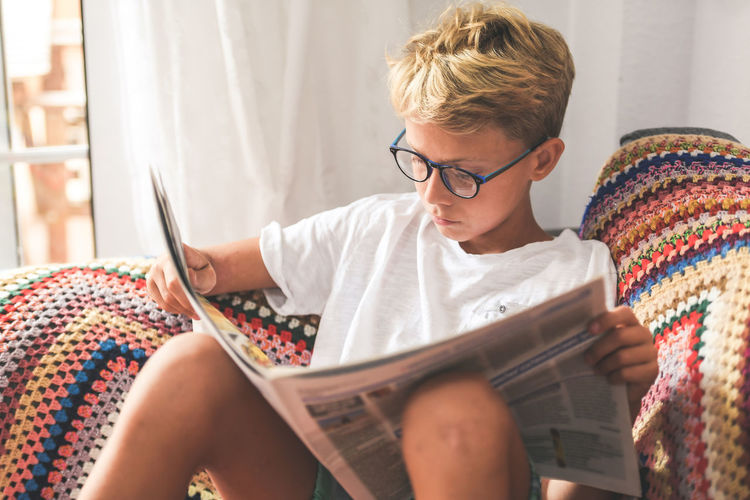 Boy reading newspaper at home