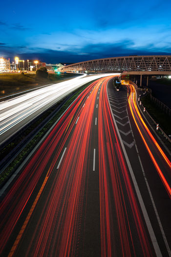 Speeding cars at the german Autobahn near Stuttgart Airport. Autobahn Automobile Blue Hour Car City Commuting Connection Connectivity Head Lights High Angle View Highway Light Trail Long Exposure Motion Motion Blur Multiple Lane Highway Night Outdoors Road Rush Hour Speed Tail Lights Traffic Transportation Travel Traveling Home For The Holidays Traveling Home For The Holidays