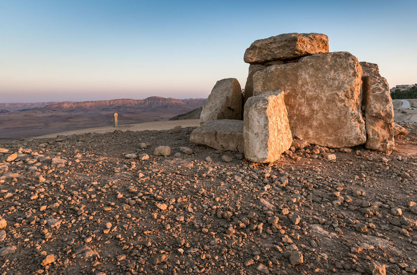 Several cutted stones placed one on another standing at sunset on the cliff of the mountains against the background of the Judean desert in Israel Isolated Light Scenic Background Beutiful Place  Cutted Stones Decorative Ecology Environment Hill Israel Journey Judean Desert Landmark Landscape Mountains Cliff Nature Rock Scenics - Nature Sky Solid Sunset Tourism Tranquil Scene Travel Destinations