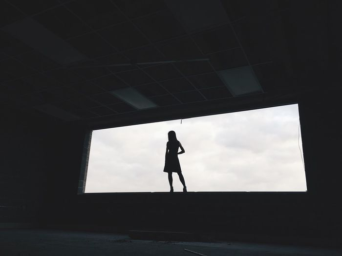 Low Angle View Of Silhouette Woman Standing On Window Against Sky