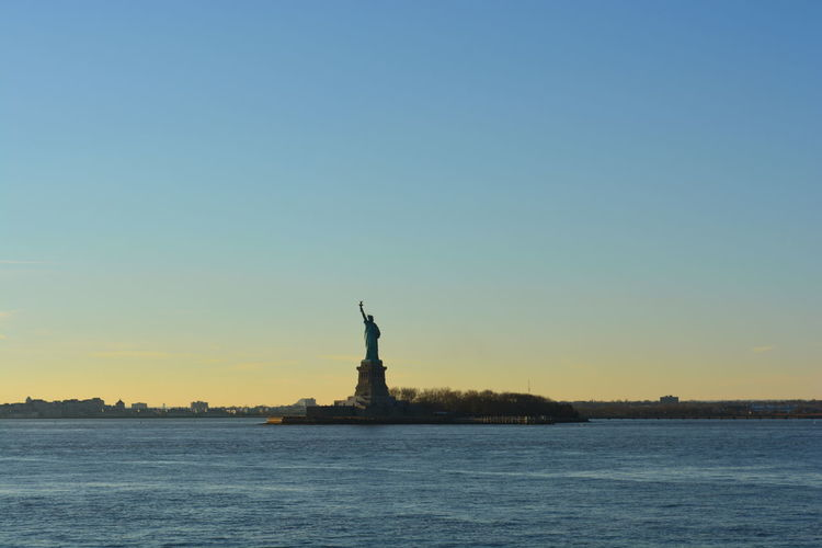Statue of liberty by hudson river against clear sky during sunset