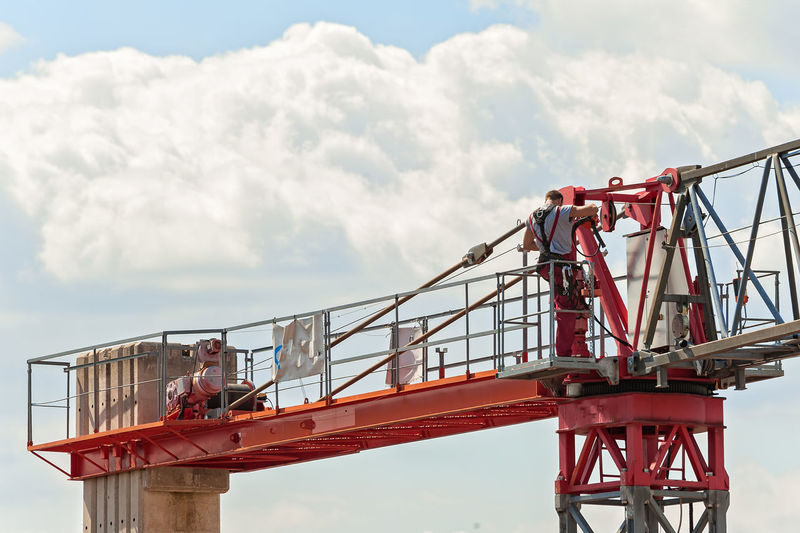 Low angle view of man standing crane against cloudy sky