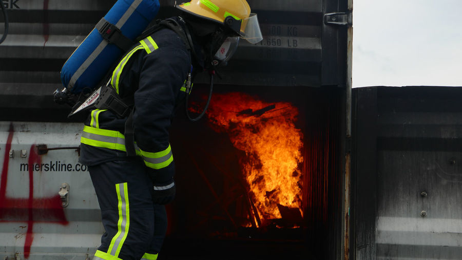 Side View Of A Firefighter In Uniform Against Fire