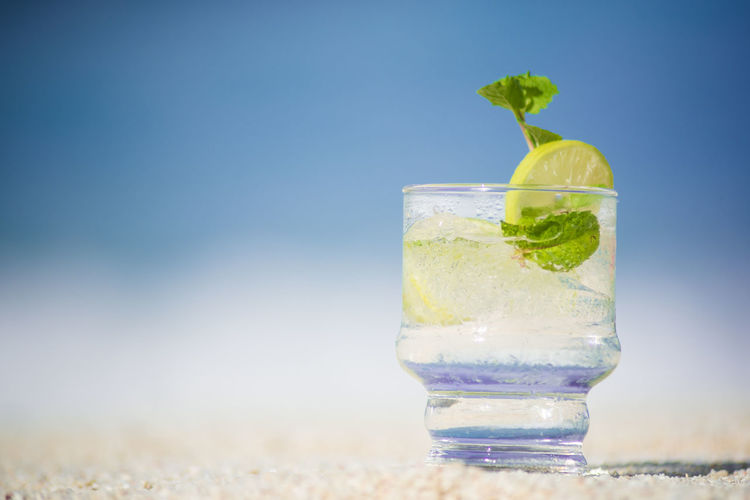 Close-up of drink on beach