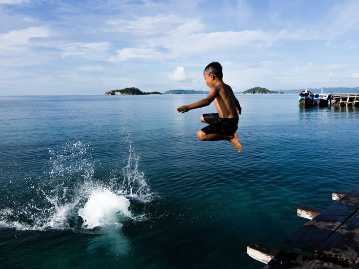 Boy jumping into sea against sky