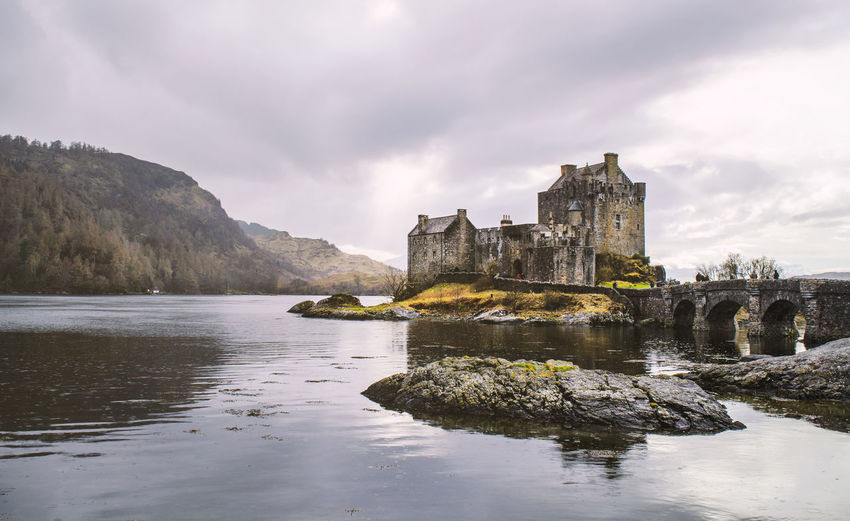 River by eilean donan castle against cloudy sky