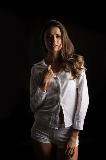 Studio Shot Black Background Young Adult Standing Three Quarter Length Indoors  One Person Front View Looking At Camera Beauty Long Hair Women Young Women Adult Fashion Beautiful Woman Portrait Hair Hairstyle Contemplation Dark
