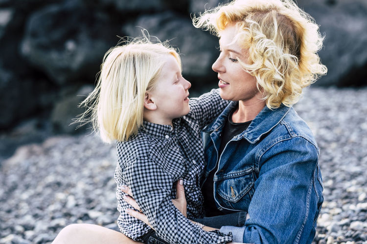 Young mother with child son looking eachother outdoor with love and fun - divorced mommy with beautiful kid hugging and smiling together forever - family concept and parents couple loving Two People Togetherness Women Blond Hair Love Adult Hair Emotion Bonding Females Positive Emotion Child Mid Adult Women Focus On Foreground Men Leisure Activity Happiness Smiling Casual Clothing Hairstyle Outdoors Daughter Son Mother Side View Beach Sunset Sun Positive Vibes Love Divorced 6-7 Years 30-34 Years
