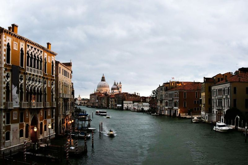 Grand canal amidst buildings against cloudy sky