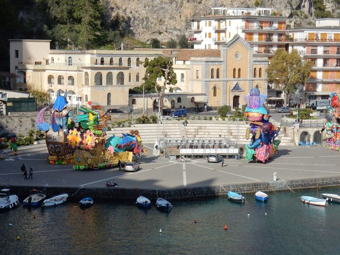 Maiori, Campania, Italy - March 4, 2019: Allegorical floats in the square of the port for the 46th edition of the Grand Carnival of Maiori Italy Campania Salerno Italy Grand Carnival Of Maiori Amalfi Coast Colorful Floats Carnival - Celebration Event Allegorical Floats Maiori, Day Architecture Building Exterior City Transportation Water Mode Of Transportation Group Of People Incidental People People Outdoors Full Length Real People Nautical Vessel Street