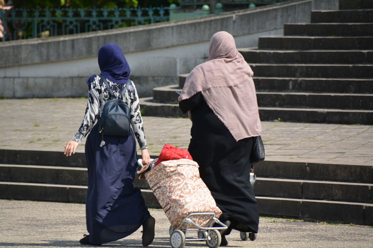 Rear view of muslim women walking with luggage on footpath in city
