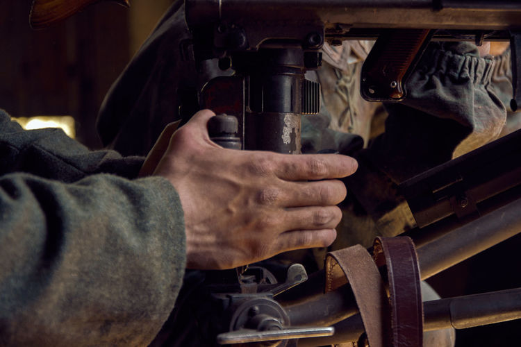 Cropped hand of man working on machine