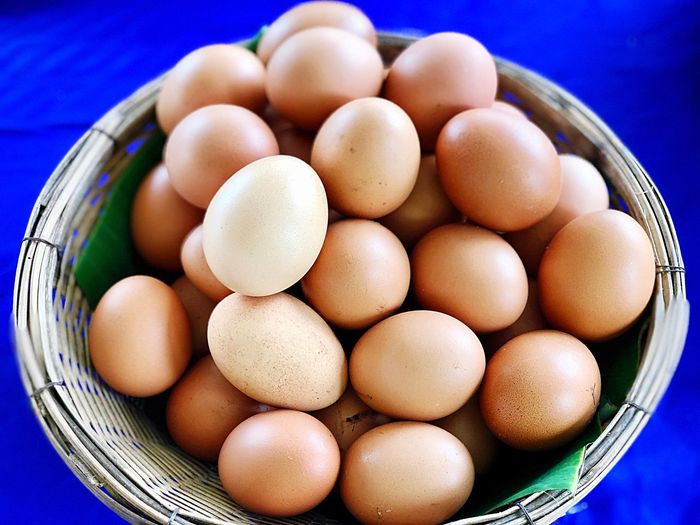 Group of eggs lay down in brown wooden texture basket on blue background Healthy Food Proteins Easter EyeEm Selects Egg Food And Drink Food Raw Food Freshness Healthy Eating Egg Carton Indoors  No People Close-up Fragility Day