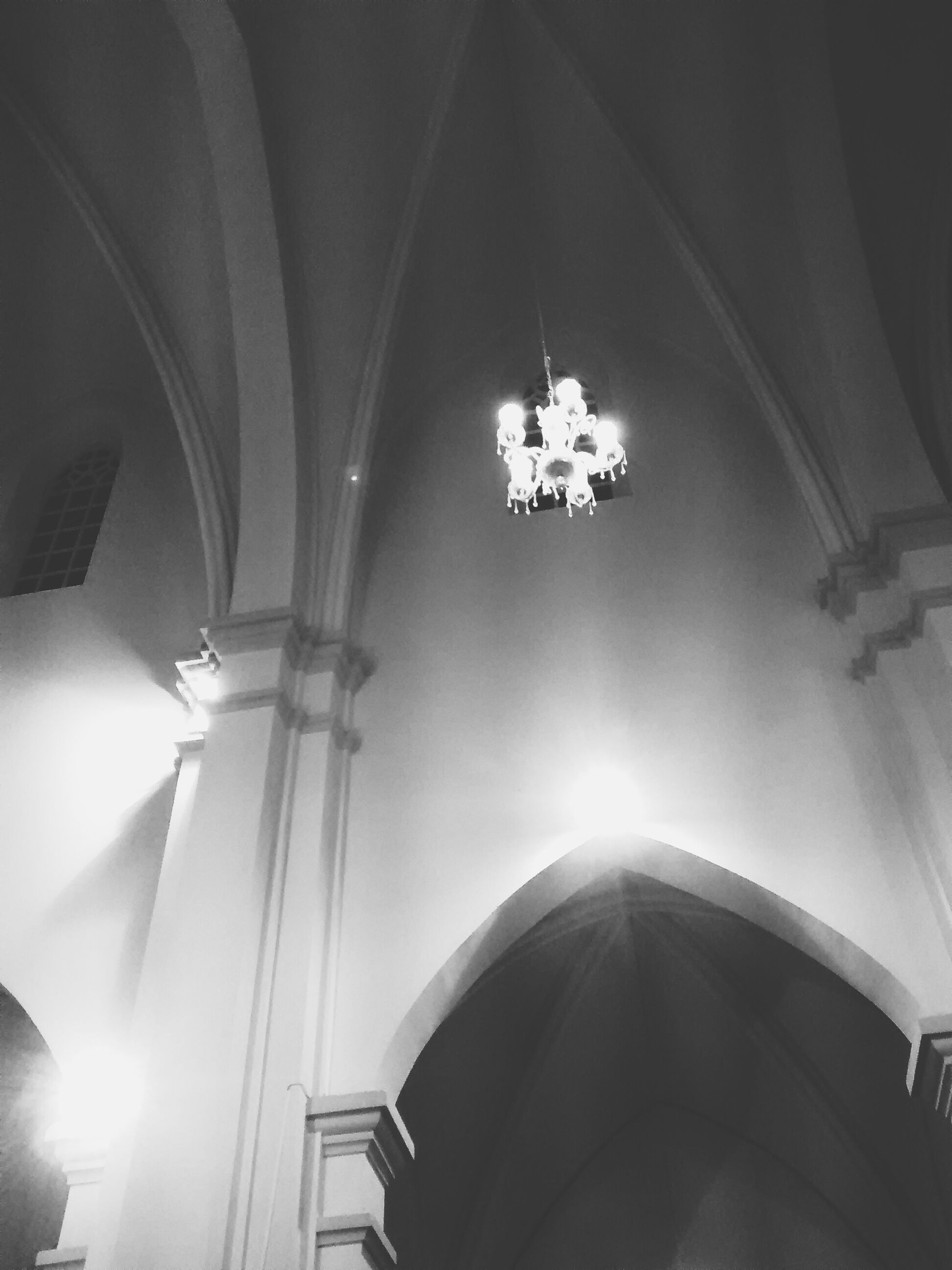 low angle view, indoors, architecture, church, illuminated, built structure, religion, lighting equipment, arch, place of worship, ceiling, travel, spirituality, hanging, no people, modern, travel destinations, technology