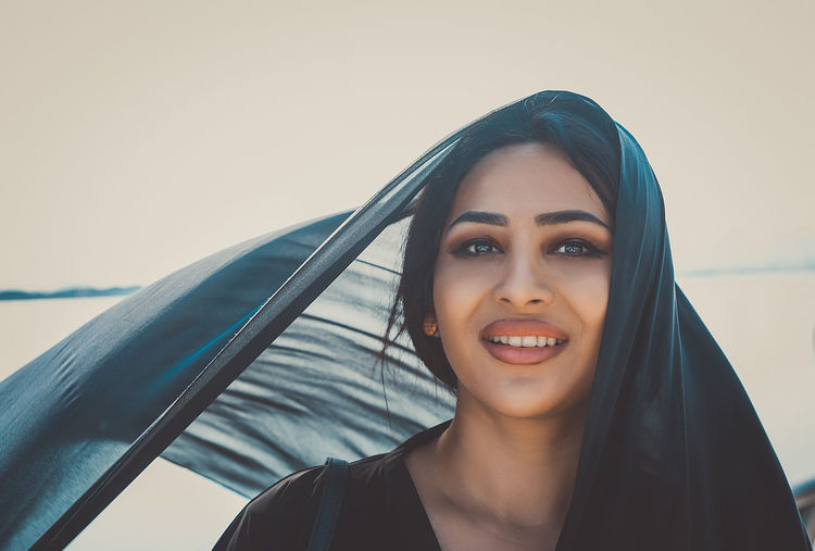 Portrait of smiling woman wearing headscarf against clear sky