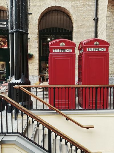 Red telephone booth by building