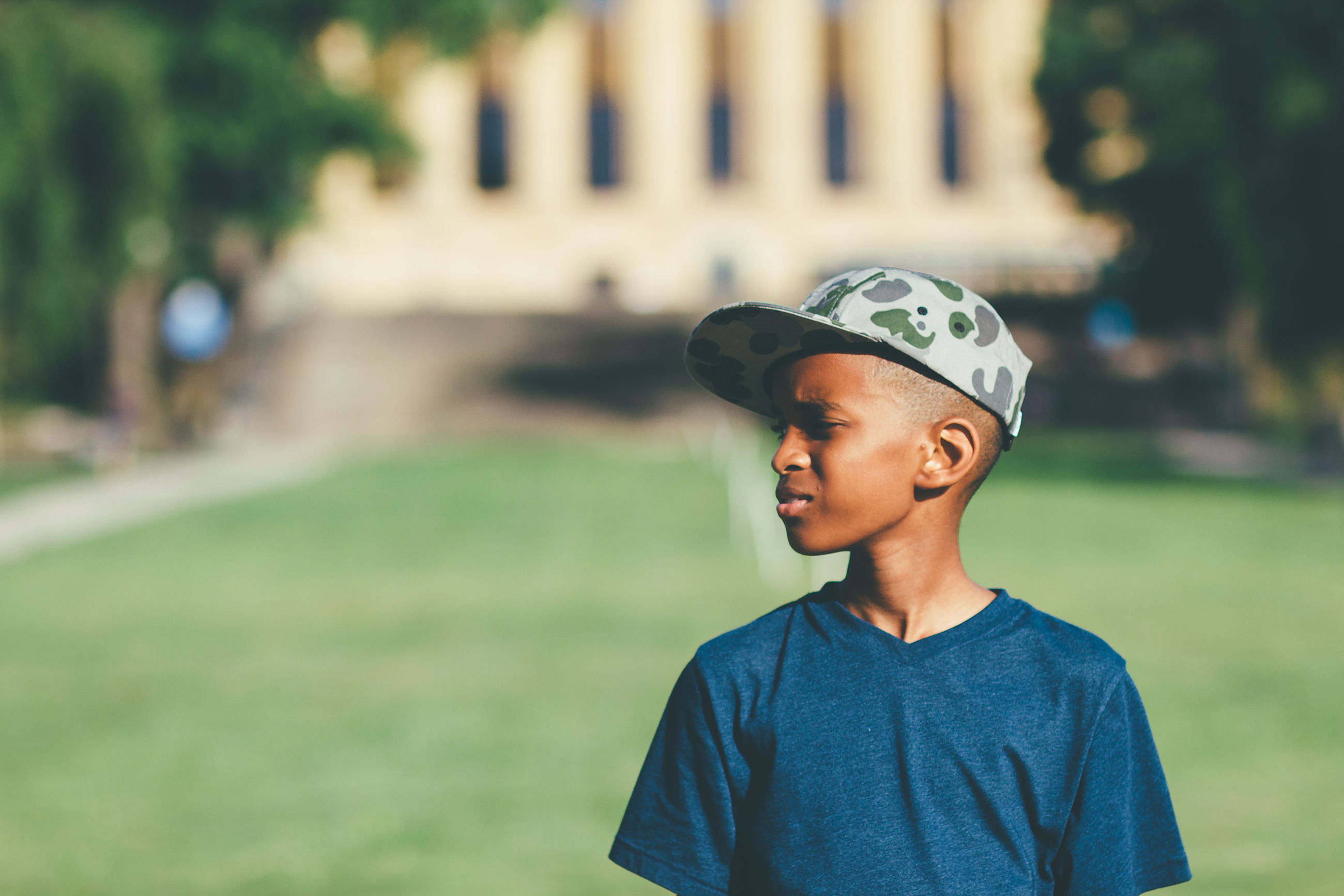 Boy with hat looking away while standing on field