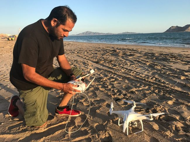 Rubén Dario Betancourt fotógrafo y videografo tiene su drone sobre la arena de la playa de bahia de Kino en una tarde soleada , en la Imagen se ve al fondo la isla de Alcatraz y el mar del Golfo de California . Hermosillo, Sonora Mexico Fly Ocean Sea EyeEm Selects Beach Sea One Person Sand Real People Standing Full Length Outdoors Mammal Nature Adults Only Adult Water Sky People Animal Themes Day
