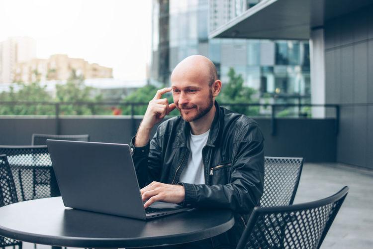 Smiling man using laptop while sitting outdoors