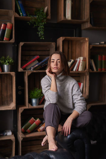 Portrait of woman sitting against shelf