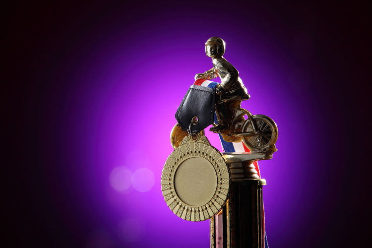 bicycle trophy on the purple background AWARD Achievement Celebration Champion Effort First Place  Golden Shiny Trophy Ceremony Competition Cup Cycling Glow Honor Leadership Light Spot Medal Metal Prize Purple Sport Success Victory Winner