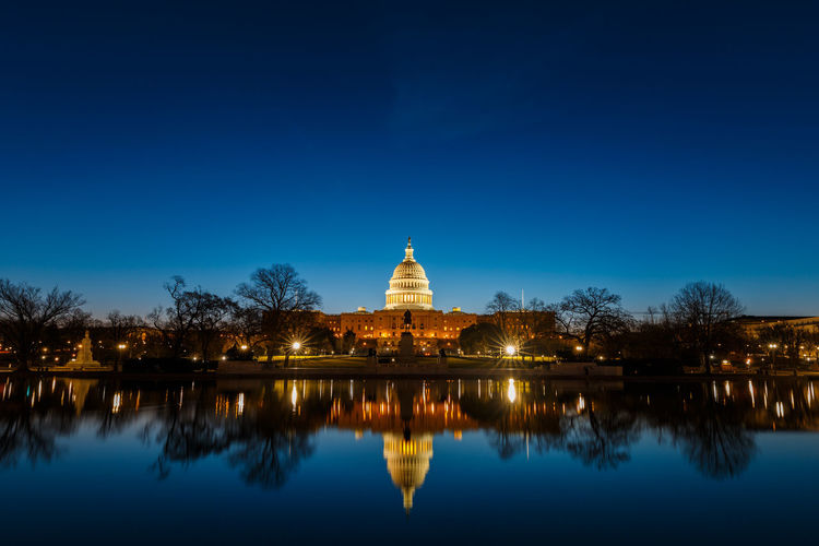 Illuminated united states capital dome with reflection on river at night