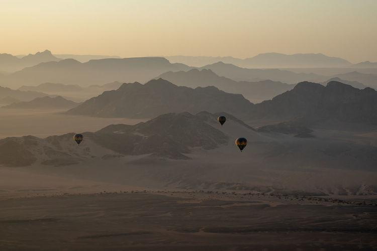 Hot air balloons flying over mountains against sky during sunrise, namib desert