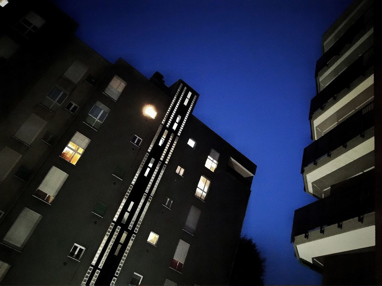 LOW ANGLE VIEW OF ILLUMINATED BUILDINGS AGAINST CLEAR SKY AT DUSK