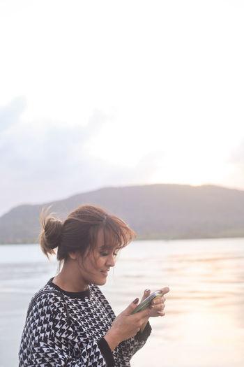 Woman using mobile phone against sea