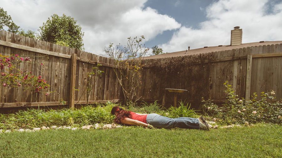 Woman lying down on land against sky