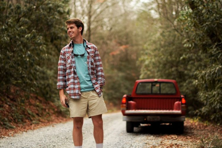 Happy Young Man Standing On Road At Forest With Off-Road Vehicle In Background