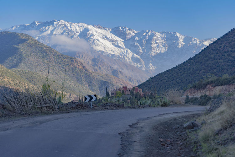 Mountain Mountain Range Sky Day Road Mountain Road Snowcapped Mountain Snowcapped Mountains Ridgeline Valley Light Light And Shadow Morocco Atlas Mountain Atlas Mountains North Africa Steep Road Cliffside Road Signs Clouds And Sky Transportation No People Mountain Peak Tranquil Scene Scenics - Nature